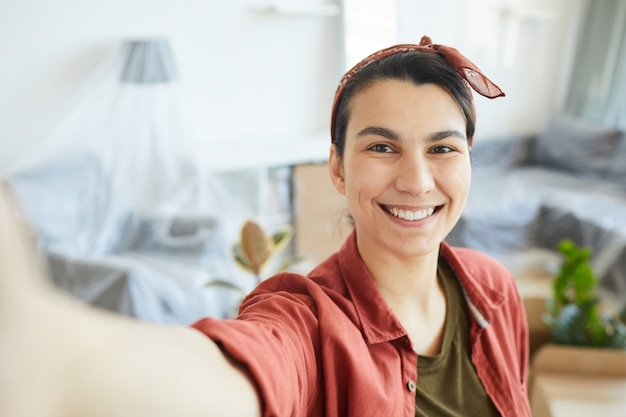 Portrait of happy young woman making selfie portrait at home