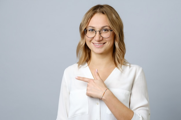 Portrait of a happy young woman pointing fingers away