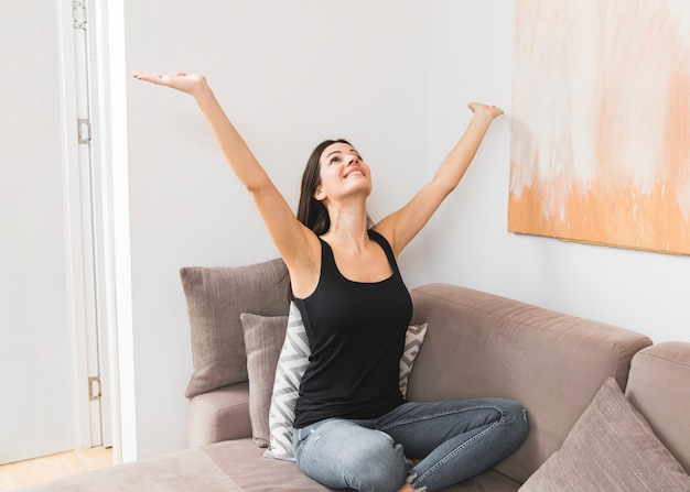 Portrait of a happy young woman sitting on sofa raising her hands looking up