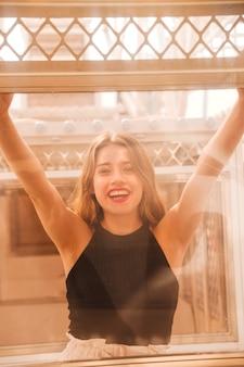 Ritratto di felice giovane donna in piedi dietro la finestra di vetro