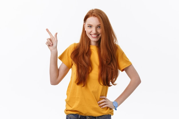 Portrait of happy young woman standing isolated over white wall