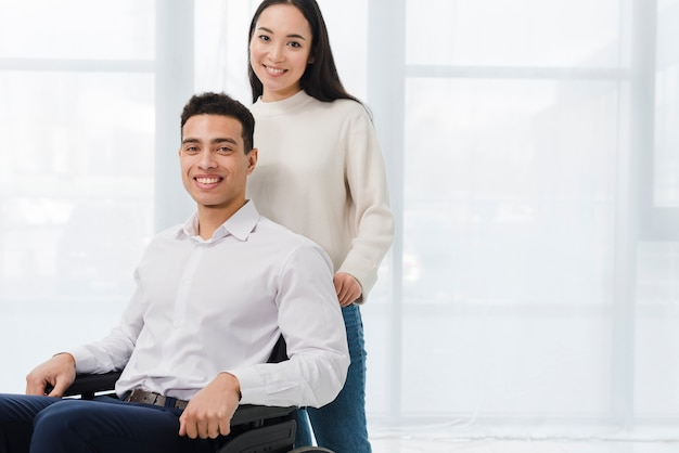Portrait of a happy young woman standing behind the man sitting on wheelchair