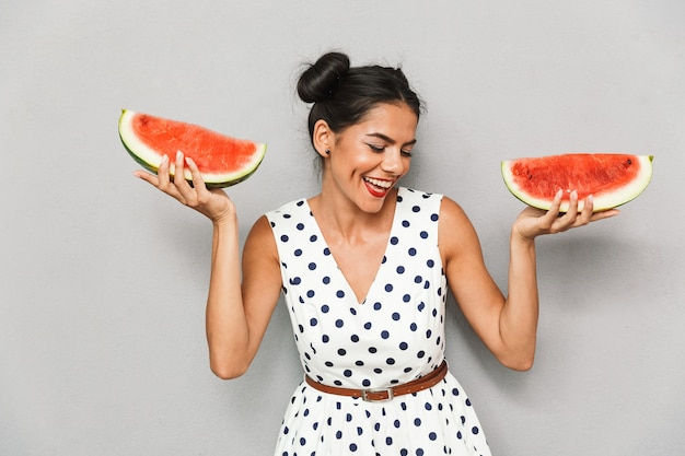 Portrait of a happy young woman in summer dress isolated, holding two watermelon slices