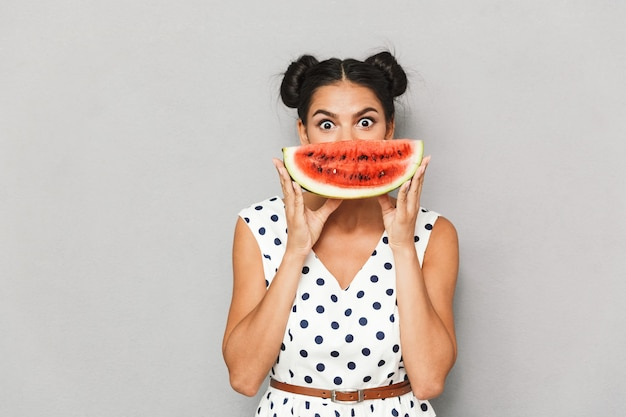 Portrait of a happy young woman in summer dress isolated, holding watermelon slice