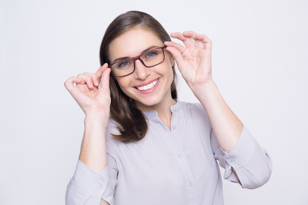 Portrait of happy young woman trying on eyeglasses