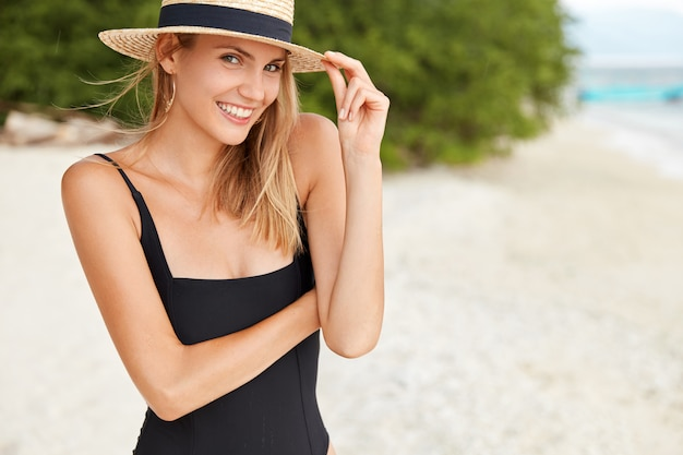 Portrait of happy young woman wears bathing suit and summer straw hat, walks on beach