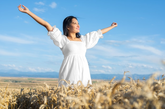 Portrait of happy young woman in a white dress on a wheat field lifestyle and happiness concept woma...