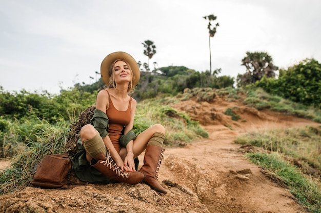 Portrait of happy young woman with backpack exploring wild steppe. stylish hipster girl in hat and boho style clothes. travel and wanderlust concept. amazing atmospheric moment