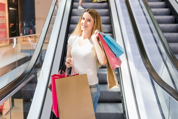 Portrait of a happy young woman with shopping bags on mall escalator