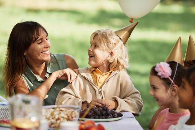 Portrait of happy young woman with son sitting at picnic table with group of kids during outdoor bir...