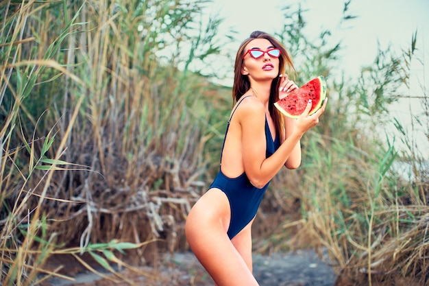 Portrait of a happy young woman with watermelon on the beach youth lifestyle