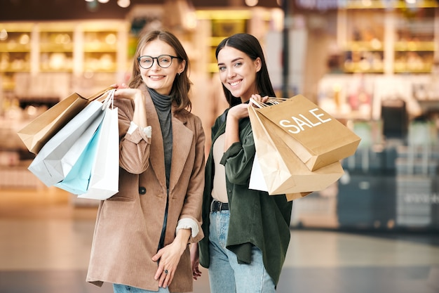 Portrait of happy young women in casual outfits holding heap of paper bags in shopping mall