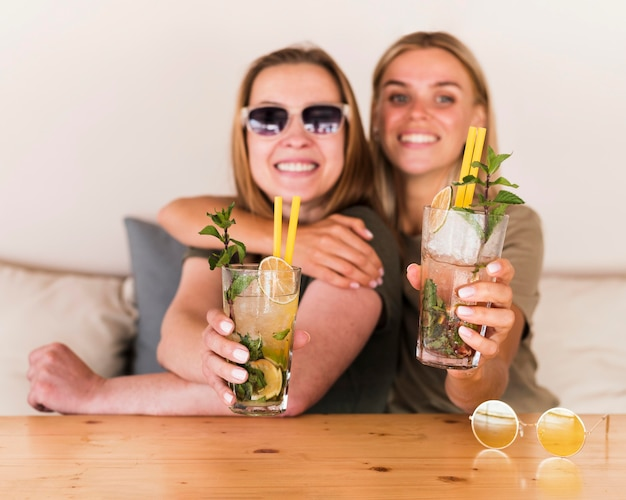 Portrait of happy young women enjoying drinks