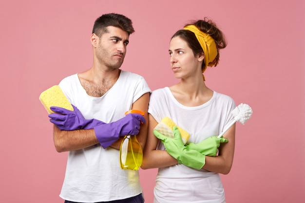 Portrait of hard-working couple looking at each other with dissatisfied look while holding sponges, spray and brush not knowing from what to begin cleaning. discontent couple having daily routine