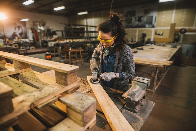 Portrait of hardworking professional female carpenter working with sandpaper and choosing wood in the workshop