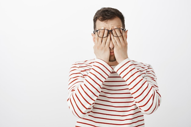 Portrait of hardworking tired adult male in striped pullover and glasses, rubbing face with palms, feeling tired and resting after hard day