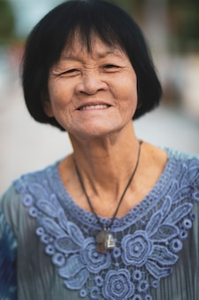 Portrait headshot of old asian woman toothy smiling face