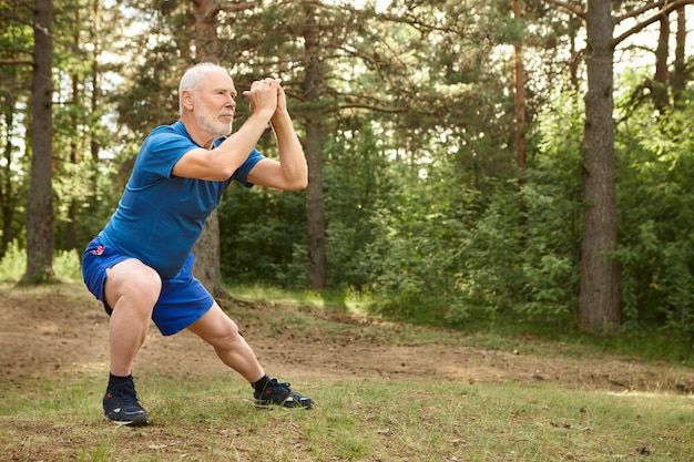 Portrait of healthy active elderly male pensioner in running shoes exercising outdoors, holding hands together in front of him and doing side lunges, having focused concentrated facial expression