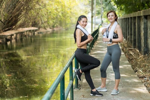 一緒に立っている肖像画の健康なアジアの大人の女性は、朝のスポーツ布を警告するフレンドリーな外観。