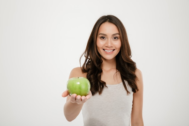 Portrait of healthy beautiful woman smiling and showing green juicy apple on camera, isolated over white