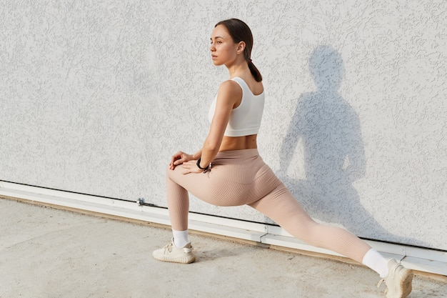 Portrait of healthy brunette young woman stretching before fitness and exercise
