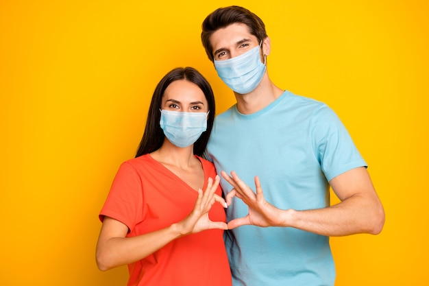 Portrait of healthy couple guy lady embracing show heart shape wear safety mask stop cov infection