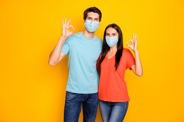 Portrait of healthy couple guy lady embracing showing ok-sign wearing safety mask stop infection