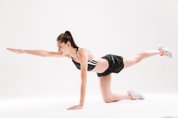 Portrait of a healthy fit sportswoman holding balance during exercise