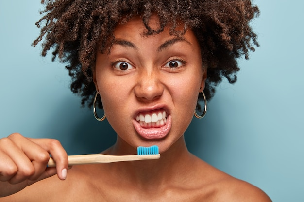Portrait of healthy girl brushes teeth, holds wooden brush, has morning routine, curly hair, poses indoor over blue wall, shows bare shoulders awakes early. people, ethnicity and hygiene concept