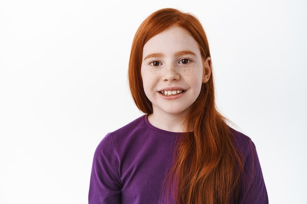 Portrait of healthy and happy redhead little girl with freckles, smiling with teeth and looking joyful at front