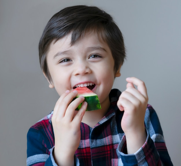 Portrait healthy kid eating fresh watermelon