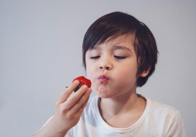 Портрет здоровый ребенок ест клубнику, селективный фокус голодный мальчик смотрит на клубнику на руке с улыбающимся лицом, ребенок пробует свежую клубнику, здоровая летняя еда для детей