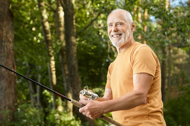 Portrait of healthy smiling bearded caucasian male pensioner in t-shirt posing outdoors with green trees holding fishing rod, enjoying angling . recreation, leisure and nature concept