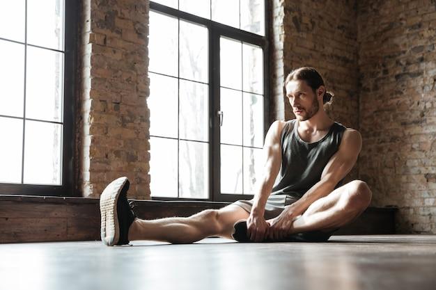 Il ritratto di uno sportivo in buona salute che fa l'allungamento si esercita