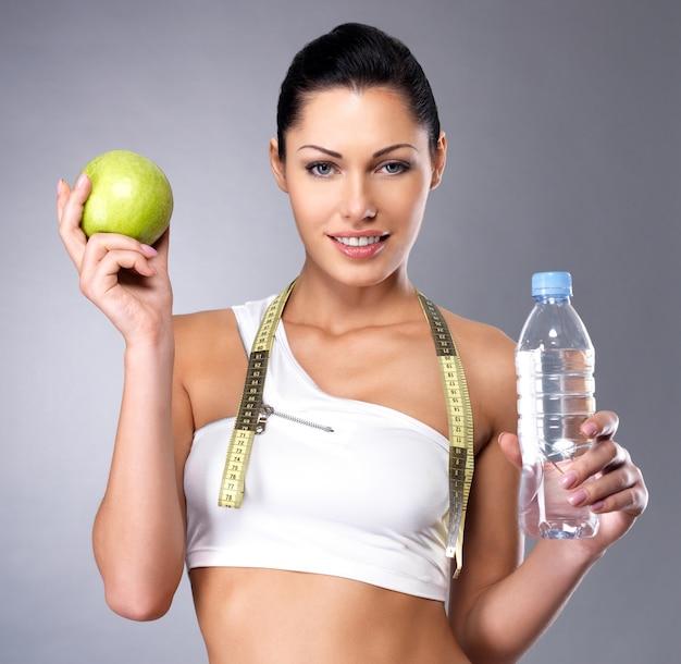 Ritratto di una donna sana con mela e bottiglia d'acqua. una sana forma fisica e mangiare il concetto di stile di vita.