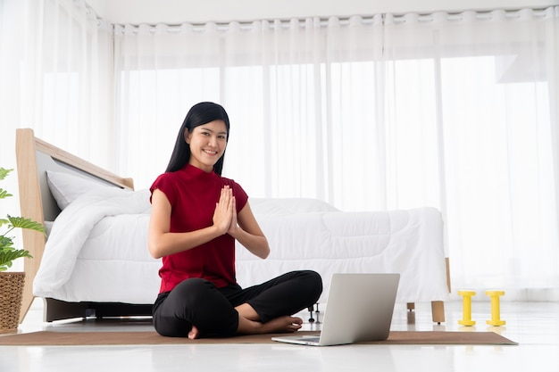 Portrait of healthy young asian woman practicing yoga exercises sitting in the bedroom