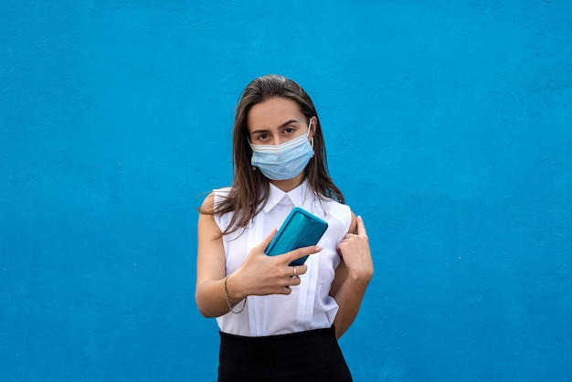 Portrait of healthy young business lady wearing medical mask with cell phone on blue background. concept of 2020  year with covid19