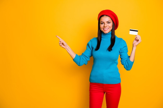Portrait of her she nice attractive cheerful cheery girl showing atm card online shopping buying purchase order new novelty copy space isolated on bright vivid shine vibrant yellow color wall