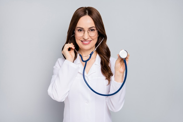 Portrait of her she nice attractive cheerful confident wavyhaired doc examining client patient diagnostic center clinic listening heart beat isolated over grey pastel color background