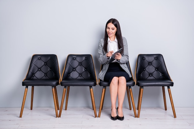 Portrait of her she nice attractive cheerful friendly confident lady realtor financier marketer sitting chair reading e-book gadget showing index rate investment isolated pastel gray color background
