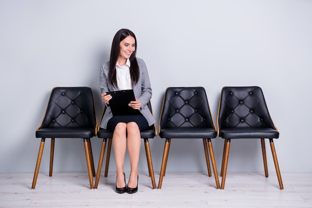 Portrait of her she nice attractive cheerful friendly confident lady representative realtor sales marketer sitting in chair talking to invisible client  isolated pastel gray color background