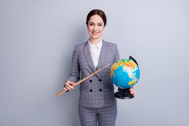 Portrait of her she nice attractive cheerful intellectual tutor wear checkered suit holding in hand globe demonstrating country map planet climate ecology isolated on grey pastel color background