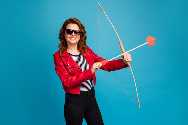 Portrait of her she nice attractive cheerful wavy-haired girl shooting affection arrow searching finding life partner match making isolated over bright vivid shine vibrant blue color background