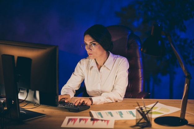 Portrait of her she nice attractive chic smart clever intellectual lady top executive manager ceo boss chief professor preparing audit result deadline annual report at night dark work place station