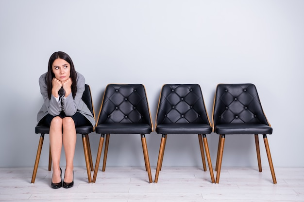 Portrait of her she nice attractive classy bored sad depressed fired lady executive finance manager realtor sitting in chair waiting meeting ceo boss chief isolated pastel gray color background