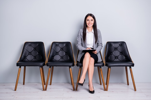 Portrait of her she nice attractive classy cheerful confident lady sales market executive manager sitting in chair writing plan strategy anti crisis isolated pastel gray color background