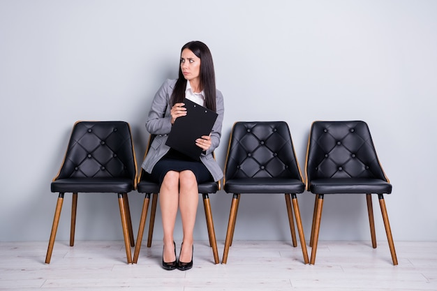 Portrait of her she nice attractive classy scared worried lady sales manager realtor sitting in chair holding insurance contract looking aside isolated pastel gray color background