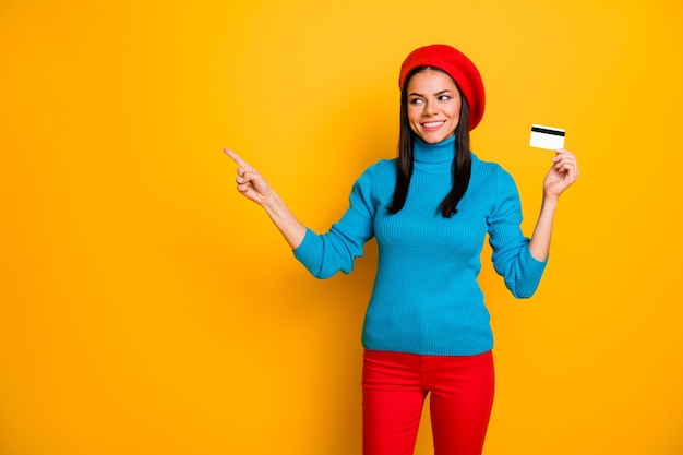 Portrait of her she nice attractive confident cheerful cheery girl showing atm card online banking shopping new service copy space isolated on bright vivid shine vibrant yellow color wall