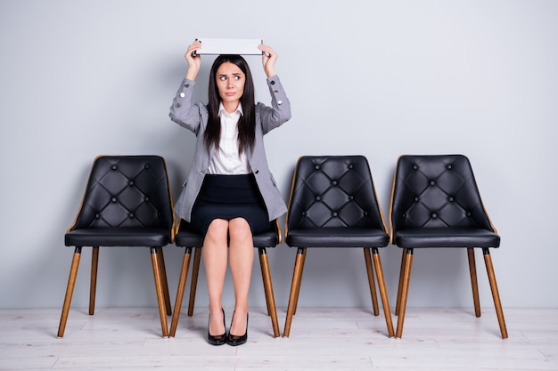 Portrait of her she nice attractive discontent scared lady realtor sales manager sitting in chair holding document over head like roof insurance protection isolated pastel gray color background