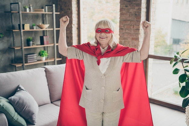 Portrait of her she nice attractive excellent strong powerful cheerful cheery glad gray-haired granny wearing red costume showing muscles at industrial brick loft modern style interior house